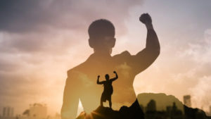person standing on hilltop with fist in the air